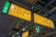 Internationell flygplats Schiphol med moderna ankomster och på engelska avvikelsetecken royaltyfri bild
