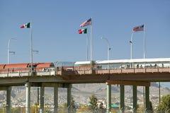 Internationell gräns av Mexico & Förenta staterna, med flaggor och gåbron som förbinder El Paso Texas till Juarez, Mexico fotografering för bildbyråer