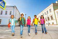 Internationella skolbarn går och rymmer händer Royaltyfria Bilder