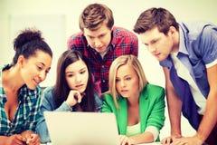Internationella studenter som ser bärbara datorn på skolan Arkivbild