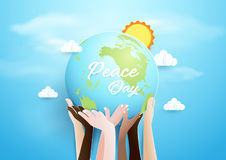 Internationnal Peace Day concept. Hands holding globe over sky. Royalty Free Stock Images