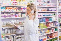 Interne de pharmacie téléphonant tout en lisant le presse-papiers image stock