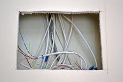 Internetów kabli rozsypisko w kwadratowej dziurze pod ścianą, przemysłów szczegóły, Zdjęcia Royalty Free