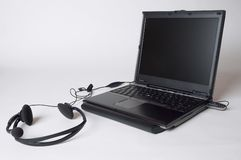 Internet. Close up of a laptop and earphones with a microphne Royalty Free Stock Photography