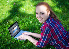 Internet access concept - happy teenage girl lying with laptop o Royalty Free Stock Photography