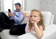 Internet addict father using mobile phone ignoring little sad daughter bored lonely and depressed stock images