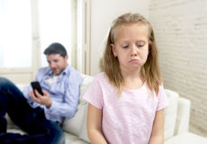 Internet addict father using mobile phone ignoring little sad daughter bored lonely and depressed. Young internet addict father using mobile phone ignoring his Royalty Free Stock Photography