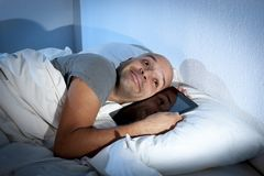 Internet addict man awake late at night in bed sleeping with digital pad or tablet Royalty Free Stock Image