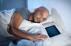 Internet addict man awake late at night in bed sleeping with digital pad or tablet Royalty Free Stock Images