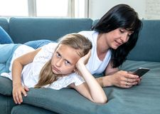 Internet addicted mum using her smart phone ignoring her sad lonely child. Digital technology addicted mum using her smart phone ignoring her sad Little girl royalty free stock images