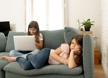 Internet addicted young girl using laptop ignoring her sad lonely younger sister royalty free stock photography