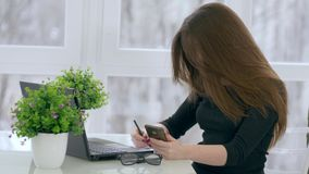 Internet addiction, beautiful girl uses mobile phone while working with laptop and notebook in modern office. Close-up stock footage
