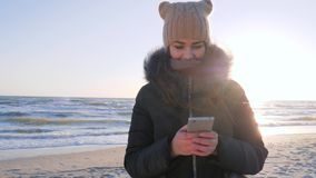 Internet addiction, girl uses mobile phone for chatting at embankment of sea in sunlight. On holiday stock footage
