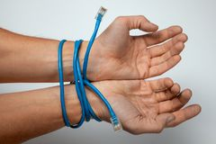 Internet addiction. Male hands are wrapped off twisted pair cable on gray background royalty free stock image