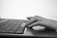Internet affair. Female hand with wedding ring and computer keyboard, concept of internet affair royalty free stock photo