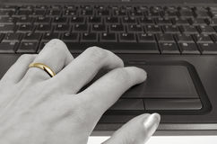 Internet affair. Female hand with wedding ring and computer keyboard, concept of internet affair royalty free stock images