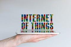 Internet av begreppet för saker (IoT) Bakgrund med den hållande minnestavlan för hand och svävatext i olika färger och med symbol arkivfoton