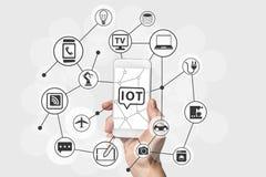 Internet av begreppet för saker (IOT) med handen som rymmer den moderna smarta telefonen för vit och för silver royaltyfri illustrationer