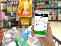 Internet av saker som marknadsför begrepp, kundbruksapplikation i mobiltelefon för att köpa en produkt i detaljhandel vid hastiga Royaltyfri Foto