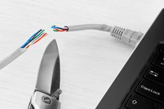 Internet ban and censorship. Internet ban, cencorship and interruption. Internet cable connected to a laptop cut by a pocket knife royalty free stock photo