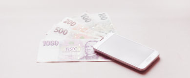 Internet banking. A white smartphone placed on czech money Royalty Free Stock Photos