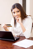 Internet banking woman. A woman doing internet banking with her laptop and credit card Royalty Free Stock Photography