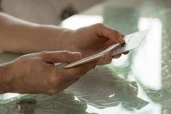 Internet-bankwezen in vrouwelijke handen tegen de achtergrond van een glaslijst Stock Foto