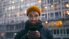 Internet bello di lettura rapida del giovane sullo smartphone alla via della città alla sera archivi video