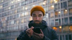 Internet bello di lettura rapida del giovane sullo smartphone alla via della città alla sera video d archivio