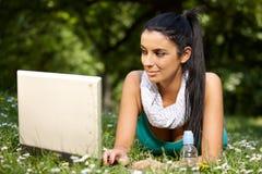 Internet bonito da consultação da menina no citypark Imagem de Stock