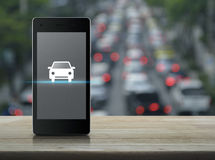 Internet business service car concept. Car flat icon on modern smart phone screen on wooden table over blur of rush hour with cars and road, Internet business Royalty Free Stock Photography