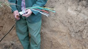 Internet cable in the ground. An employee man repairs an Internet cable in the ground stock photography