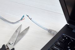 Internet cable, laptop and scissors. Concept of internet ban, cencorship and security. Internet cable connected to a laptop cut by a scissors royalty free stock images