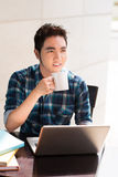 Internet cafe. Vertical image of a guy drinking coffee at the Internet cafe stock photography