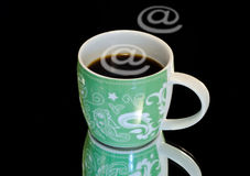 Internet- cafe. Black coffee in green cup and e-mail symbol royalty free stock photography