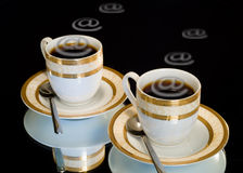 Internet-cafe. Black coffee in coffee cups and e-mail symbol royalty free stock photography