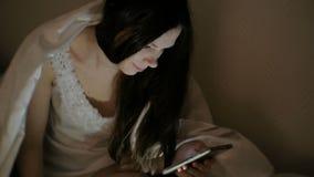 Internet castana di lettura rapida della giovane bella donna in suo telefono cellulare a letto prima del sonno video d archivio