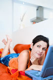 Internet chat. Young women is resting on the couch and surfing the internet on her laptop computer Stock Image