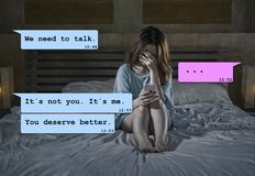 Internet chat composite with young woman desperate in bed suffering pain dumped by his boyfriend via mobile phone receiving royalty free stock image