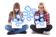 Internet chat - two teenage girls sitting with laptops isolated Royalty Free Stock Photos