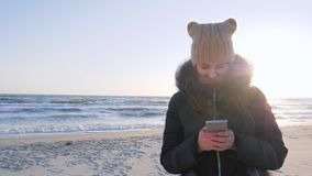 Internet communication, woman uses cell phone for chatting at waterfront of ocean. In sunlight stock video