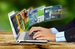 Internet Concept. Businessman hand browsing internet websites on his laptop Stock Photos