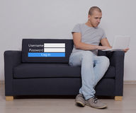 Internet concept - handsome man sitting using computer and login Stock Photo