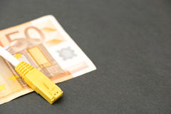 Internet costs. Network cable on a 50 euro banknote for concepts like internet costs - focus on the connector, copy space to the right Royalty Free Stock Image