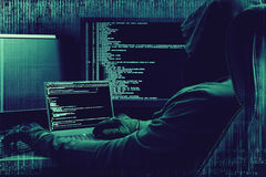 Internet crime concept. Hacker working on a code on dark digital background with digital interface around. Internet concept. Hacker working on a code on dark Stock Photography
