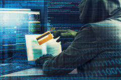 Internet crime concept. Hacker working on a code and stealing credit card with digital interface around. Internet concept. Hacker working on a code on dark Royalty Free Stock Photo