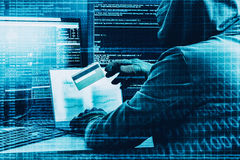 Internet crime concept. Hacker working on a code and stealing credit card with digital interface around. Stock Photography