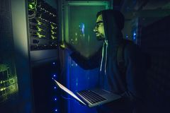 Hacker in data centre. Internet crime concept. Hooded hacker working on a code with laptop in dark data centre. Cyber security stock image