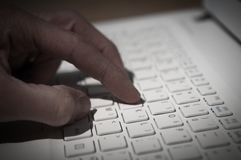 Internet crime, hand typing on a computer keyboard. In dark room stock photos
