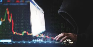 Internet crime and speculate stock concepts, Hacker working on computer laptop with downward stock graph background Royalty Free Stock Images